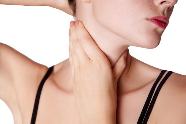 Closeup vista de uma jovem com dor no pescoço ou glândula tireóide em fundo branco.