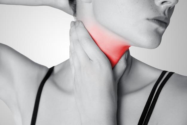 Closeup vista de uma jovem com dor no pescoço ou glândula tireóide em fundo cinza. foto em preto e branco com ponto vermelho.
