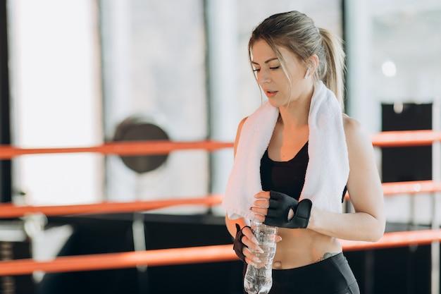 Closeup vista de uma jovem mulher em fones de ouvido sem fio, tendo uma pausa após treinamento duro pelo saco de boxe