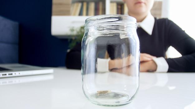 Closeup vista de uma senhora de negócios vestida de vestido preto, sentada à mesa branca em que está localizado vazio de jarras de moedas