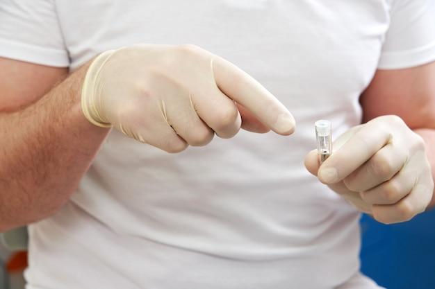 Closeup vista do dentista segurando um implante dentário na clínica médica