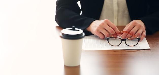 Closeup vista do empresário sentado à mesa do escritório com café para viagem, gráficos de documentos e segurando copos