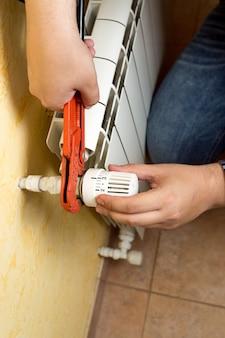 Closeup vista do homem instalando a válvula no radiador de aquecimento