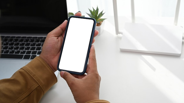 Closeup vista do homem usando um telefone inteligente e sentado na frente do roteador sem fio no escritório em casa.