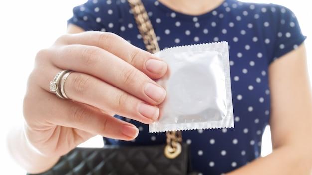 Closeup vista do pacote de preservativo na mão feminina. conceito de contracepção e segurança no sexo.