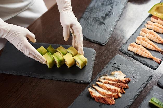 Closeup vista do processo de preparação de sushi rolante