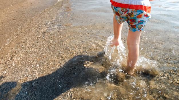 Closeup vista dos pés da criança correndo na água do mar na praia.