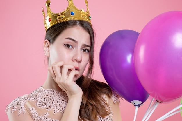 Closeup vista frontal confusa garota festeira com coroa segurando balões colocando a mão