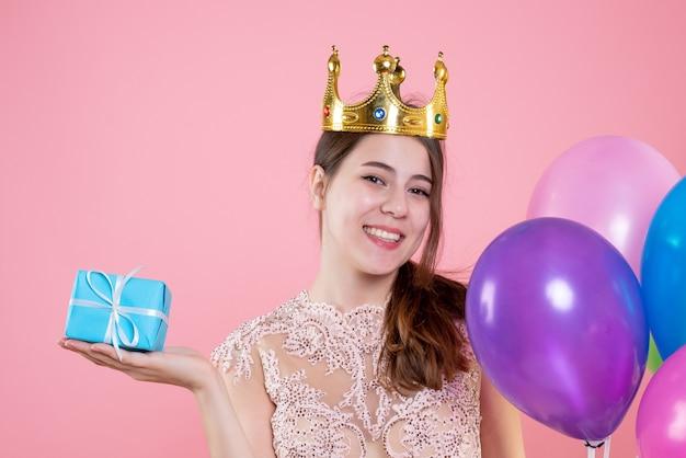 Closeup vista frontal feliz festa garota com coroa segurando um presente e balões