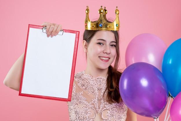 Closeup vista frontal feliz garota festeira com coroa segurando a prancheta e balões