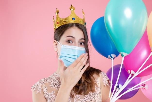 Closeup vista frontal linda garota festeira com coroa e máscara segurando balões
