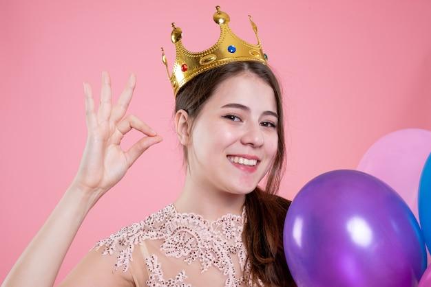 Closeup vista frontal linda garota festeira com coroa segurando balões e fazendo sinal de ok