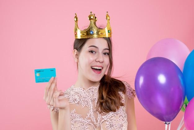 Closeup vista frontal linda garota festeira com coroa segurando cartão e balões