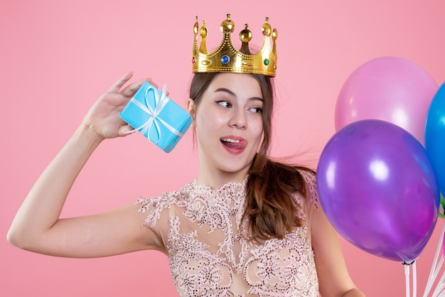 Closeup vista frontal linda garota festeira com coroa segurando um presente e balões