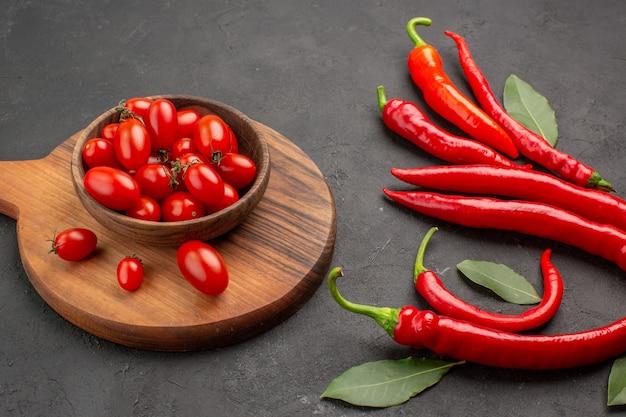 Closeup vista inferior de pimentas vermelhas e folhas de pagamento e uma tigela de tomates cereja na tábua oval de corte na mesa preta