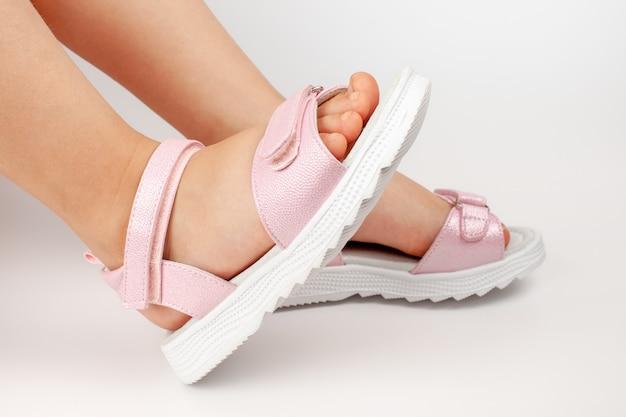 Closeup vista lateral de sandálias de couro infantil rosa com sola plana dois sapatos confortáveis no chi ...