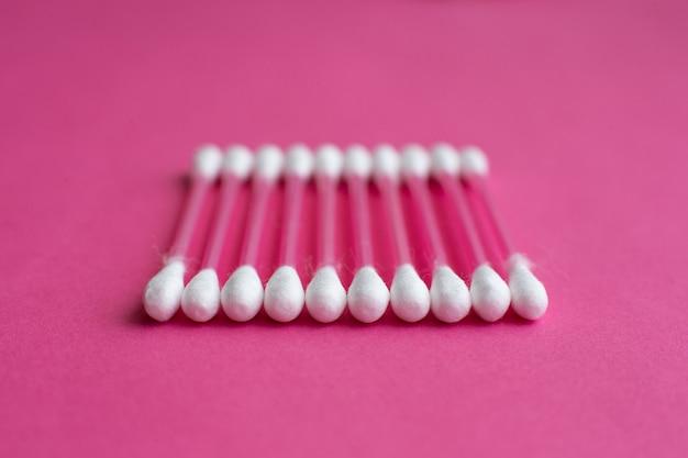 Closeup vista lateral em cotonetes colocado em uma linha horizontal no fundo rosa