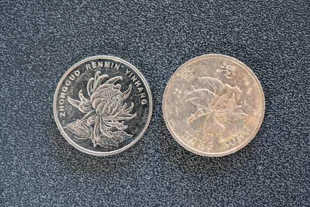 Closeup vista lateral traseira de 1 yuan chinês e moedas de 1 dólar hong kong em fundo escuro