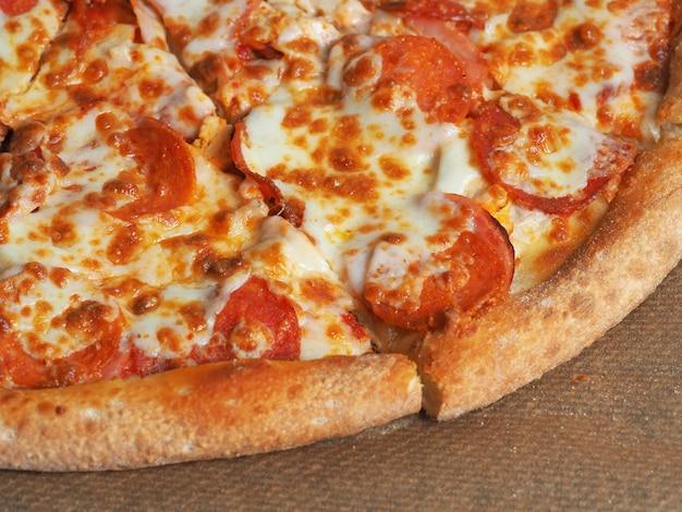 Closeup vista superior da pizza com presunto, peperoni e queijo. delicioso prato italiano em casa