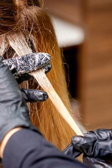 Closeup vista traseira das mãos de cabeleireiro em luvas aplicando tinta em uma mecha de cabelo de uma jovem ruiva em um salão de cabeleireiro