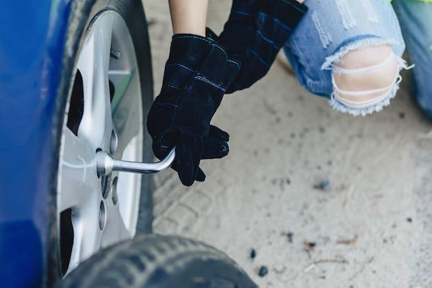 Closup mãos desmontar a roda do carro