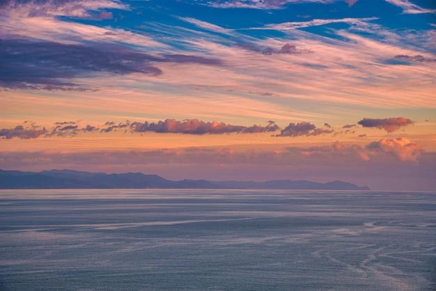 Cloudscape bonita e dramático pôr do sol sobre a montanha e o mar.