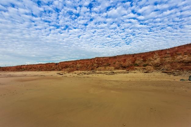 Cloudscape da praia deserta com pedras para o mar mediterrâneo