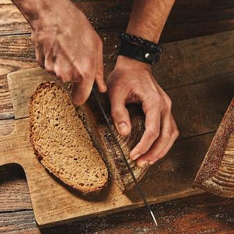 Clous up man cortando pão fresco
