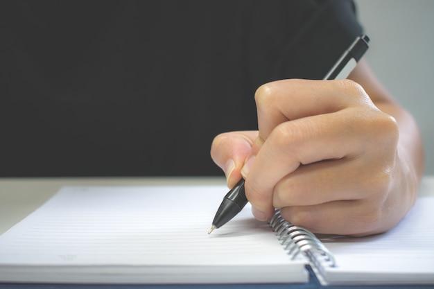 Clouse para cima. uma caneta de mão escrevendo no caderno.