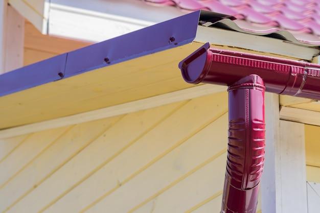 Clsoe acima da calha vermelha na parte superior do telhado da casa