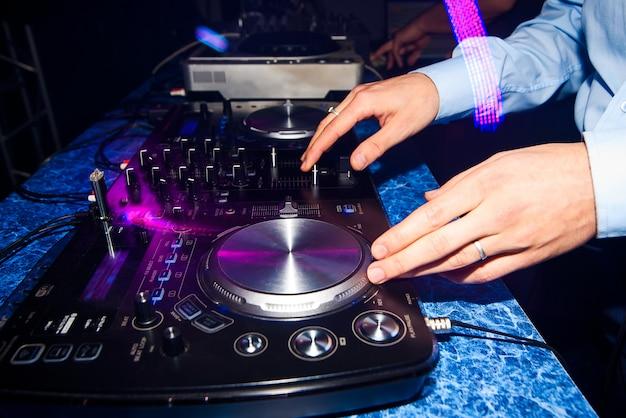 Club dj mistura de música em um mixer em uma boate