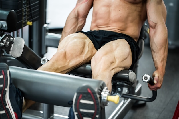 Clube de fitness ginásio interior com pesos de treinamento jovem com pernas