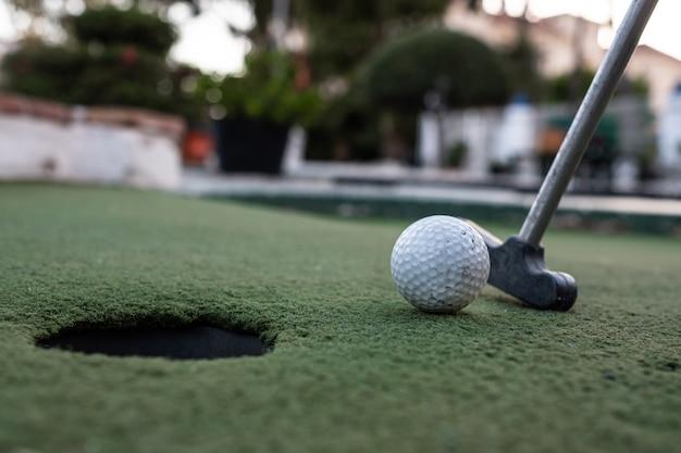 Clube de golfe, bola de golfe e buraco em um campo de minigolfe