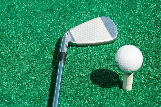 Clube de golfe e bola em um carrinho com relva artificial
