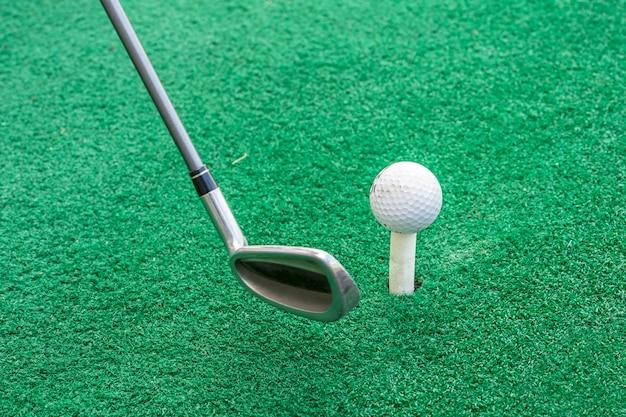 Clube de golfe e bola em um carrinho
