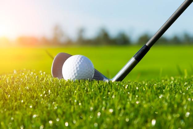 Clube de golfe e bola na grama