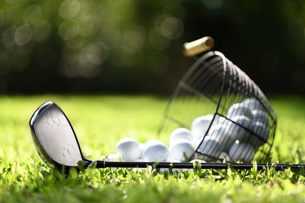 Clube de golfe e bolas de golfe na cesta na grama verde para prática
