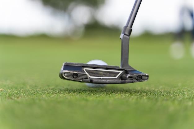Clube de golfe na frente de uma bola de golfe em um campo de golfe