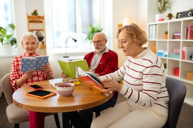 Clube de leitura. idosos simpáticos sentados com livros enquanto participam do clube de leitura