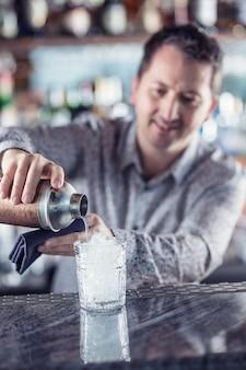Clube noturno profissional barmanin fazendo coquetel alcoólico.