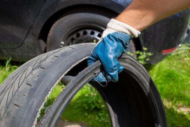 Co-conceito de unidade perigosa. a mão do mestre em uma luva azul segura o pneu rasgado com arame. fechar-se. no fundo do carro preto em um borrão