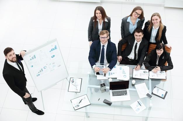 Coach de negócios ensinando funcionários no quadro branco em treinamento corporativo.