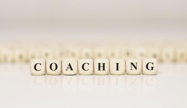 Coaching da palavra escrita no bloco de madeira. conceito de negócios.