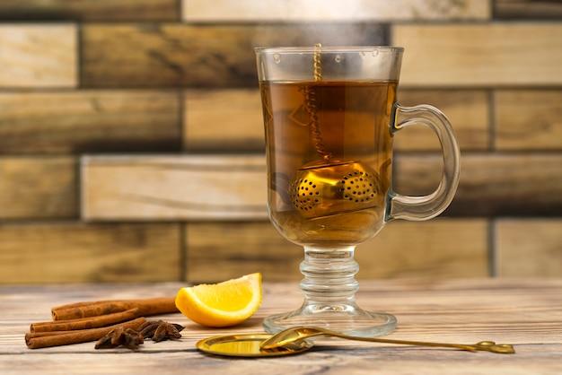 Coador de chá vintage e copo de chá em uma mesa de madeira com limão e canela