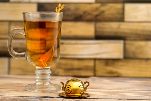 Coador de chá vintage e um copo de chá em uma mesa de madeira com lugar para texto