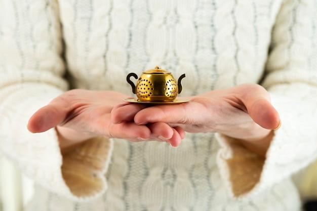 Coador de chá vintage na forma de um bule de chá nas mãos femininas