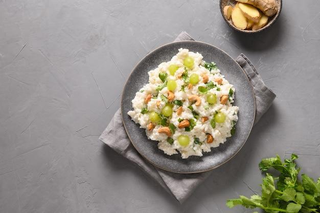 Coalhada de arroz com castanha de caju e coentro em um fundo cinza