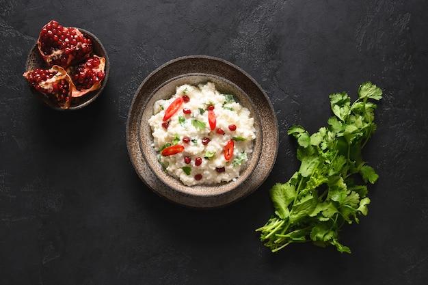 Coalhada de arroz com romã e coentro, sementes de mostarda e gengibre em um fundo preto culinária indiana