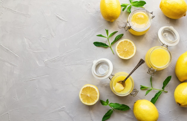 Coalhada de limão caseira fresca em potes de vidro no fundo branco de concreto. vista do topo. copie a área do espaço.