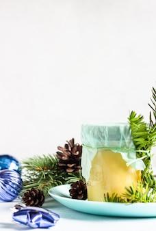 Coalhada de limão em frasco de vidro. ramos de abeto, cones e decorações de natal.